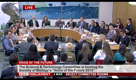 Young scientist discussing in a round table with UK's members of the parliament